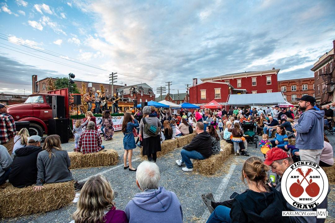 A band plays on the back of a flat bed truck while a crowd watches while sitting on hay bales during PickFest Music Festival held in Boyertown, PA