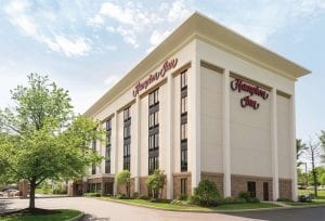 The Hampton Inn Wyomissing has five floors with a white exterior and is surrounded by trees