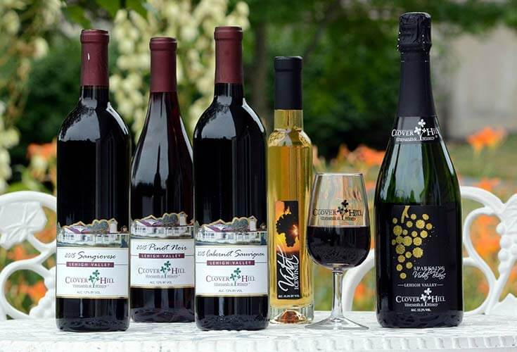 4 Bottles of wine with half full wineglass on an outdoor table at Clover Hill Vineyards and Winery in Berks County
