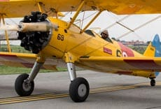 A yellow bi-plane sits on display at the WWII Weekend in Pennsylvania's Americana Region