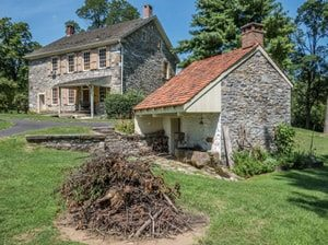 Stone House and outbuilding in summer with blue sky at Conrad Weiser Homestead in Berks County
