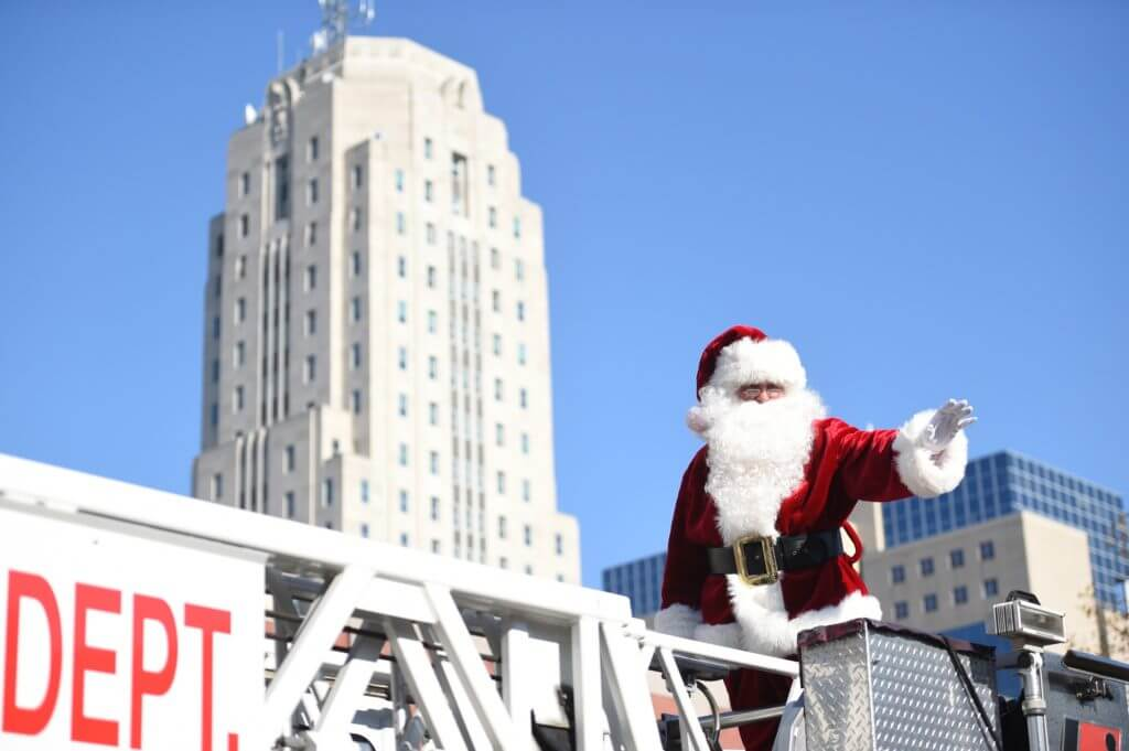 Santa Claus is on a fire truck, waving to people at the Holiday PA's Americana Region