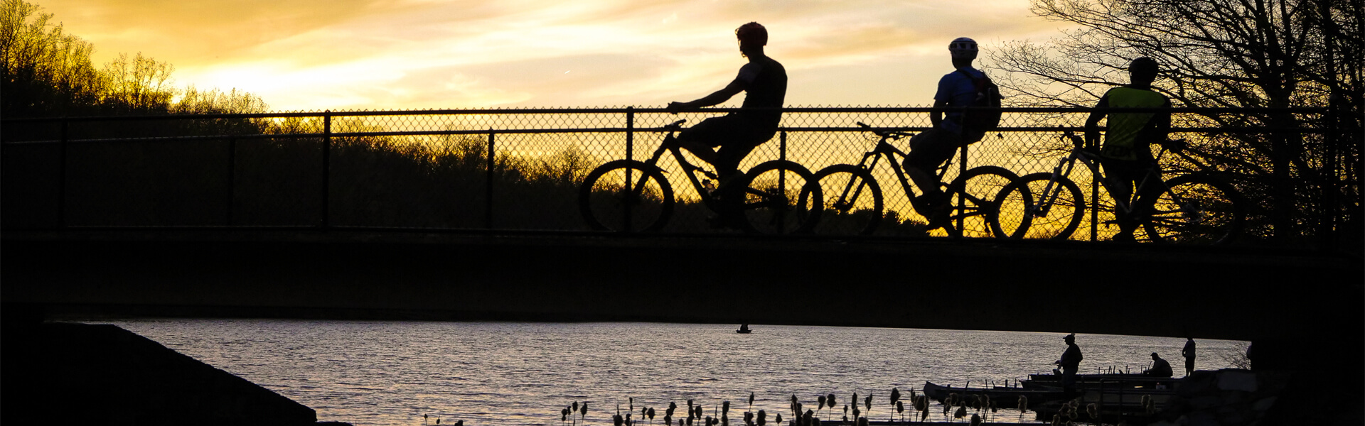 Three bicyclists on a bridge overlooking fishermen at sunset