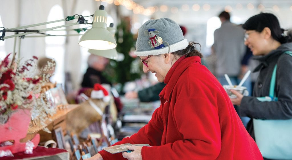 Shot of a woman in a red coat and grey mouse hat Christmas shopping.