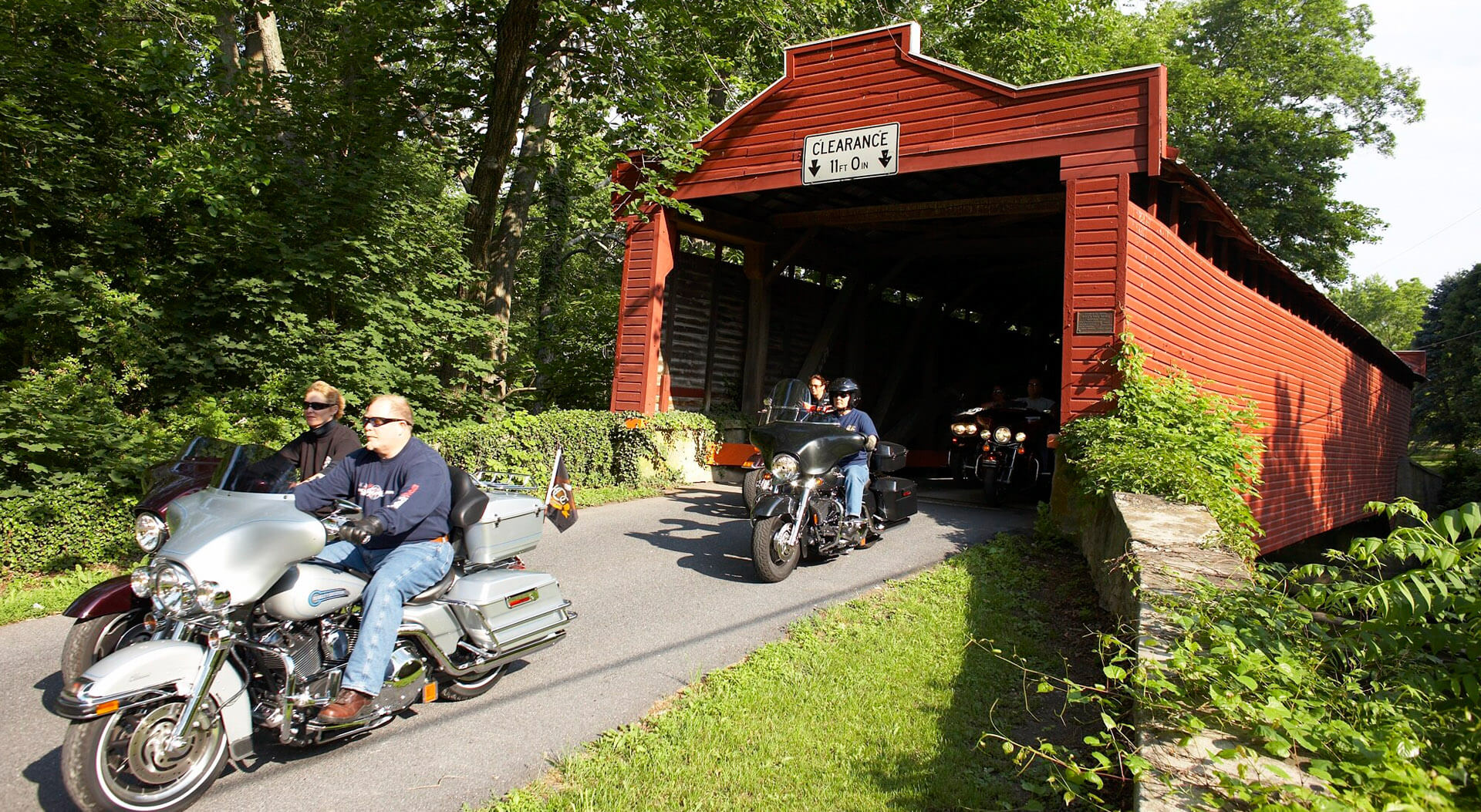 Motorcyclists riding through a red covered bridge in Berks County