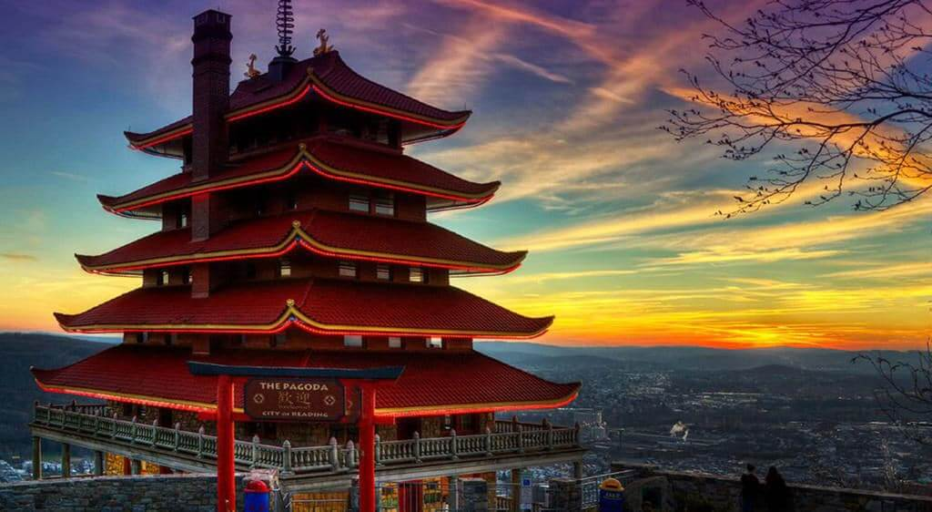 The Pagoda on top of Mount Penn overlooks the city of Reading PA in front of a picturesque sunset of blues, greens and oranges.