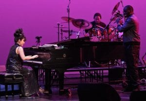 Jazz pianist Keiko Matzui performs at her piano with accompanying musicians behind her.