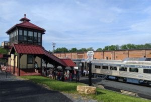Passengers leave the silver Reading Blue Mountain Railroad car and walk to a train stop with a red roof.