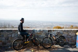 Man on a cycle sitting by a wall on Skyline Drive that overlooks the city of Reading