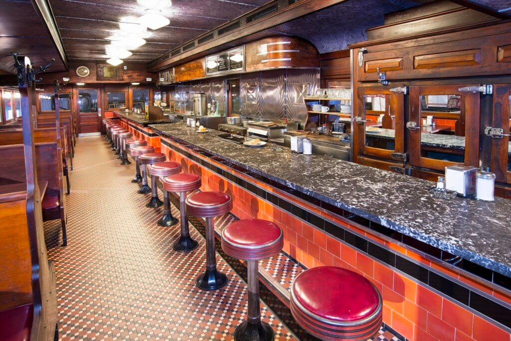Counter view of a 1930s diner car, complete with tile floor, wooden ice box and red vinyl covered stools. Visitors can see at Diner Day, one of the things to do in November