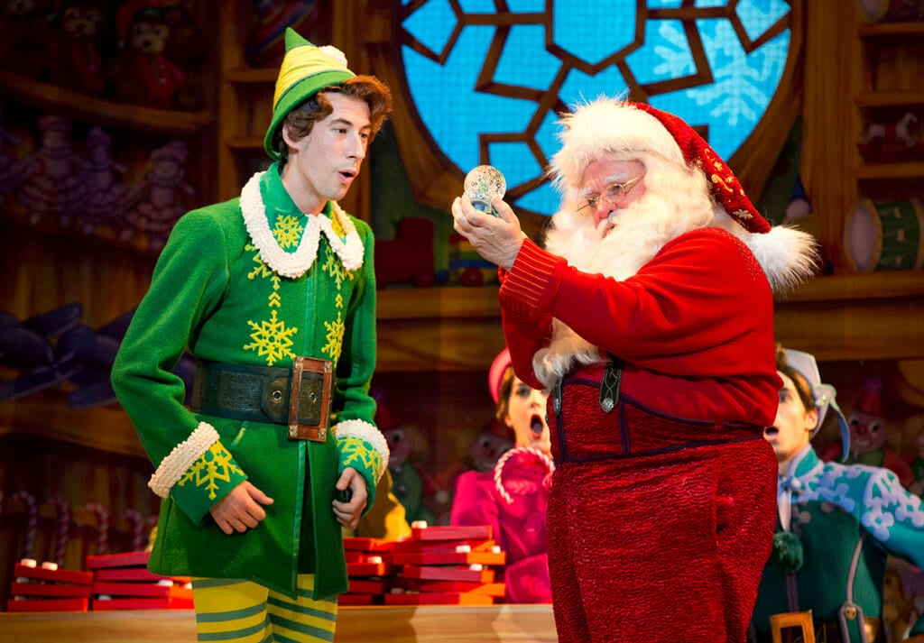 A tall, young elf, dressed in green talks with Santa Claus, one of this November's things to do.