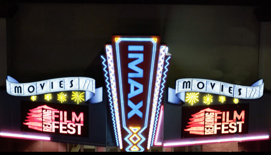 "An advertisement for Reading Film Fest that includes a marquee of a movie theatre - The Imax. IMAX ia writtten in blue with scolls with the word ""Movies"" on either side of Imax. Under one scroll is Reading Film Fest, under the other, the Reading Film Fest logo."