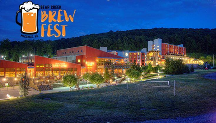 A grouping of buildings, Bear Creek Mountain Resort, can be seen against an evening sky. The logo for its Beer Fest, a drawing of a beer mug, filled with froathy beer, is on the left side of the picture.