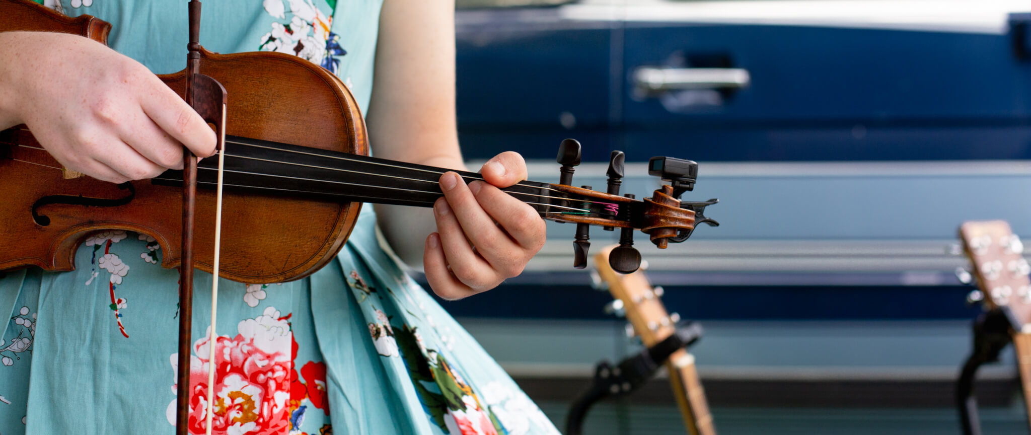Girl in a blue cotton dress with flowers playing a fiddle at the Early Bird Fiddle Fest which takes place at the Heritage Center in Berks County, PA