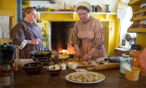 Two women dressed in PA Dutch clothing bake at Easter on the Farm at the PA German Cultural Heritage Center