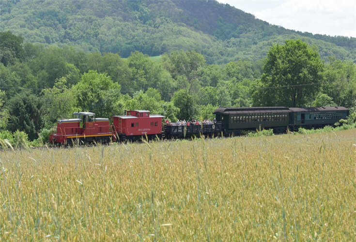 The WK&S railroad rides the tracks along side a spring cornfield with trees and a mountain behind it. The Train one of many in Pennsylvania's Americana Region.