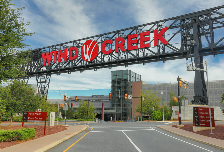 The entrance to the Wind Creek Bethlehem entrance wiith the works Wind Creek in big red letters on a steel bridge.