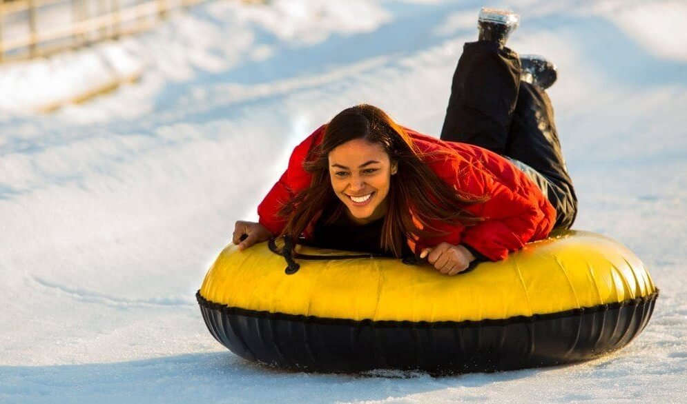 Young woman slides down a snow covered mountain in a yellow and black tube.