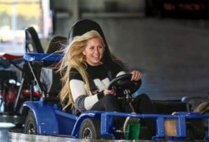 Teenage girl dressed in black pants and a wide stripe white and blue sweater driving a go kart at the Carlisle Sports Emporium near Reading, PA