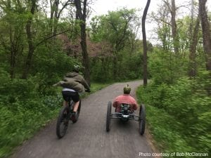 Two bikers, one on a mountain bike and one on an adaptive bike, ride the Union Canal gravel trail in Berks County, Pennsylvania