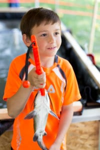A young boy holds up a catfish he caught during Get Outdoors Day in Reading, Berks County, PA
