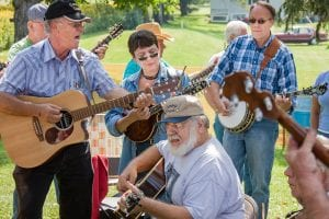 A group of musicians stand together outside playing guitars, banjos and fiddles at a fall festival.