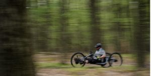 A cyclist on an adaptive bicycle rides a mountain trail with trees in the background