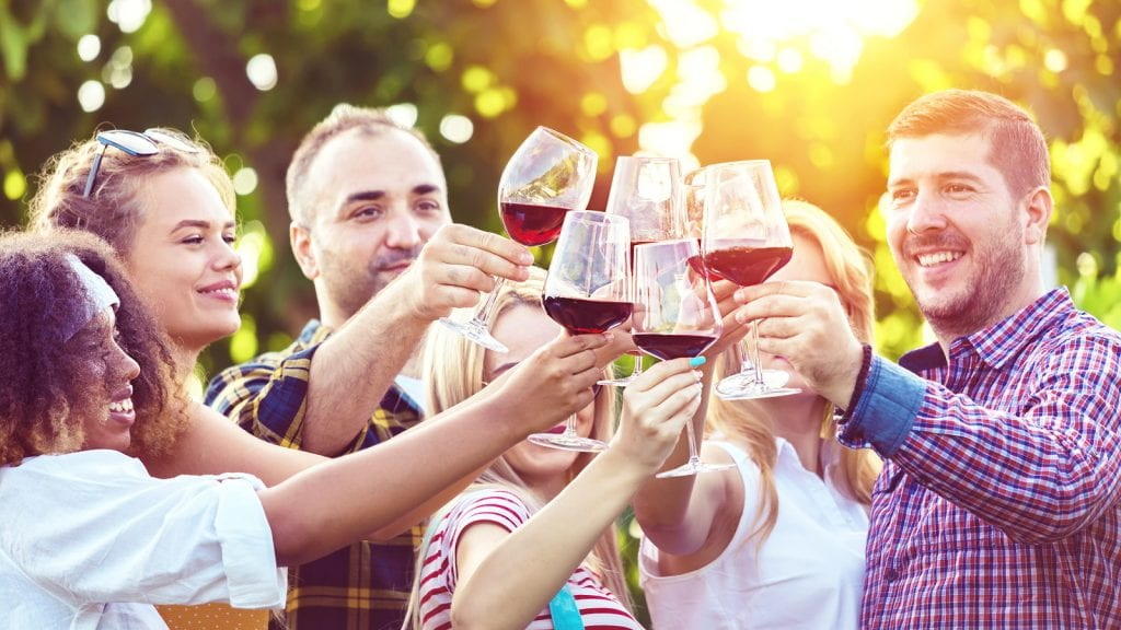 A group of friends are celebrating getting together with a wine tasting in rural Pennsylvania.