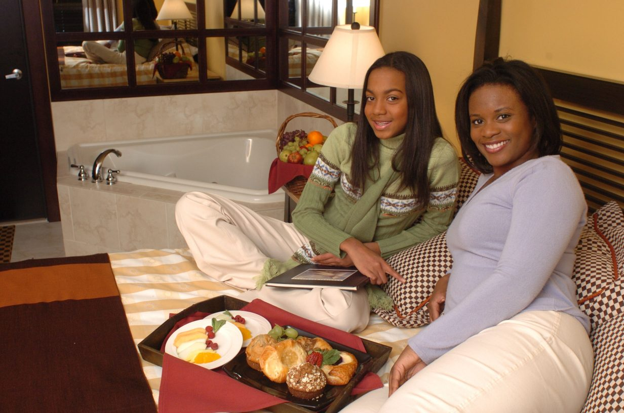 Two women enjoy room service and comfortable lodging at Bear Creek Mountain Resort while touring other locations throughout the Pennsylvania Americana Region.