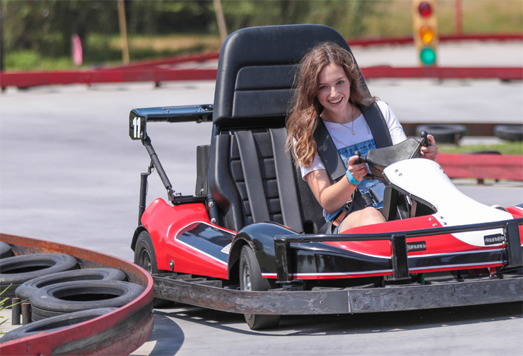 A young woman with long brown hair drives a red and black go cart at Carlisle Sports Imporium
