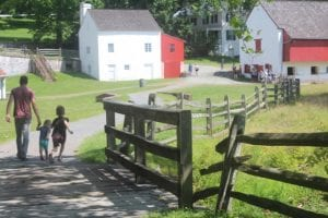 A family walks down the path through the Hopewell Furnace NHS village on a beautiful summer day.