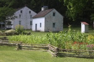 Two historic buildings stand surrounded by beautiful greeney at the Hopewell Furnace National Historic Site.