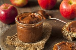 Photo of a jar of brown apple butter and spoon on wooden surface with red apples in the background.