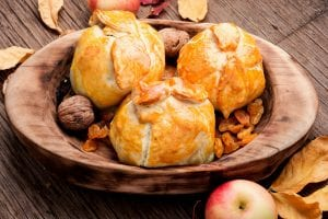 Photo of three apple dumplings in a wooden bowl with dried fruit and walnuts.