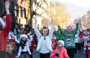 Three children in winter jackets lead the way for a group of young dancers in the Reading Holiday Parade.