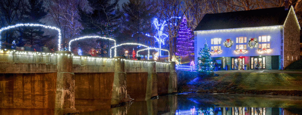 A bridge over the Tulpehocken Creek is lit up with Christmas lights next to a decorated barn