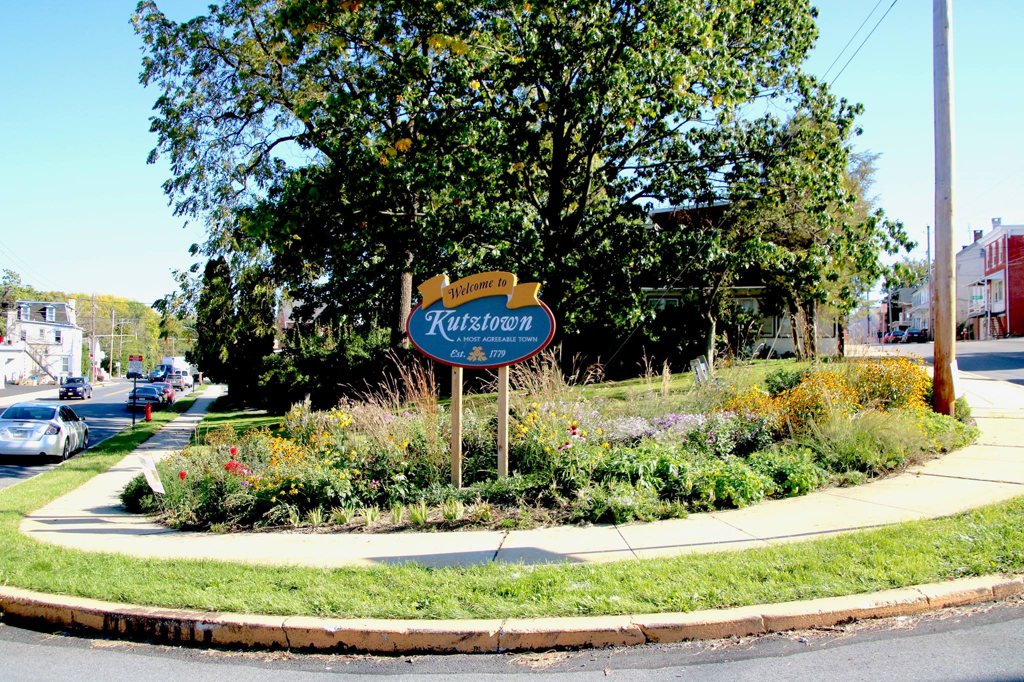 A Welcome to Kutztown sign in a flower garden in the town of Kutztown