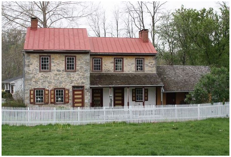 This historic building made of stone with a red roof and surrounded by a white picket fence was built in the 1800's.