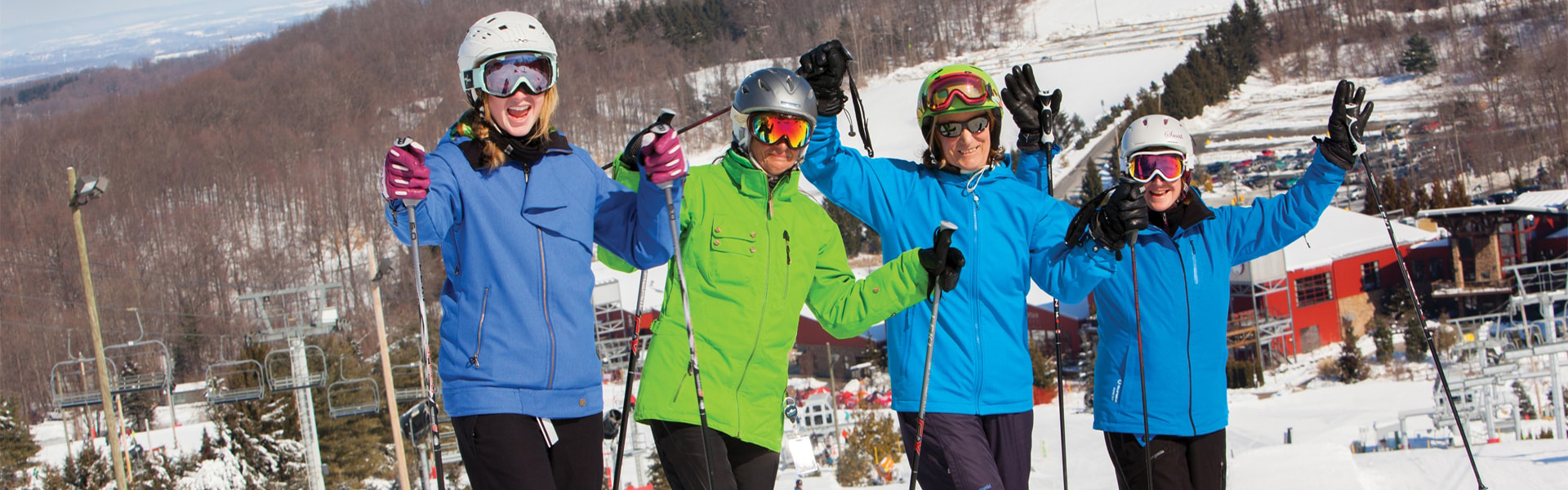 Four skiiers wearing helmets and goggles pose atop Bear Creek Mountain Resort in Berks County Pennsylvania