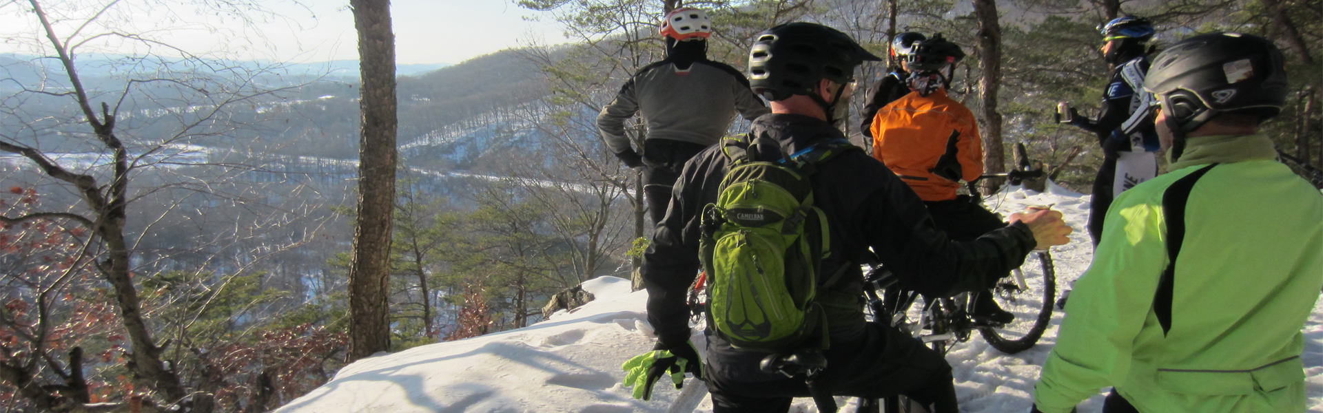 Several mountain bikers take a break from riding in the snow and enjoy the scenic overlook at Neversink Mtn. in Berks County