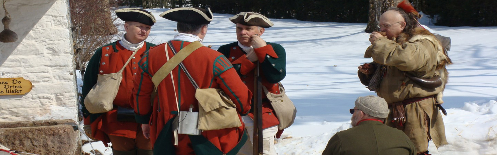 Reenactors dressed in red uniforms at the Conrad Weiser Homestead in Berks County stop to talk