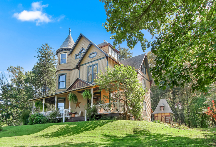 This historic home that is painted yellow with blue trim now serves as a bed and breakfast. It features a victorian turret and a relaxing front porch for guests to enjoy. It lovely front porch